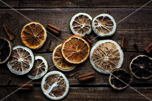 Various dried slices of citrus fruits and cinnamon sticks on wooden surface