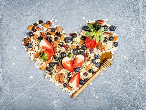 Ingredients for healthy breakfast: muesli in shape of heart