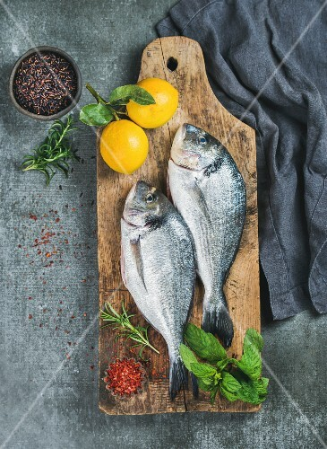 Fresh uncooked sea bream or dorado fish with lemon, herbs and spices in bowls on rustic wooden board