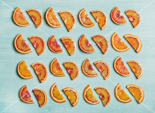 Natural fruit pattern concept. Fresh juicy blood orange slices placed in rows over light blue painted table