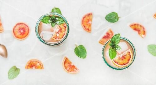 Sommer-Limonade mit Blutorangen, Eiswürfeln und Minze in Gläsern (Aufsicht)