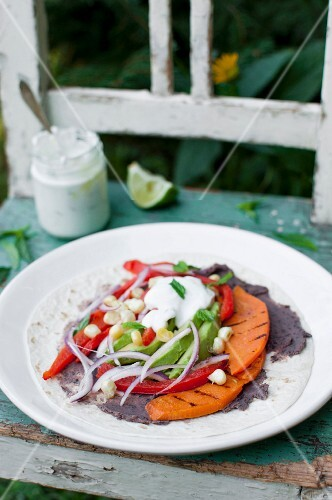 Wrap (tortilla) with black beans paste, roasted pepper, roasted sweet potato, avocado, corn grains, red onion and mint yoghurt sauce