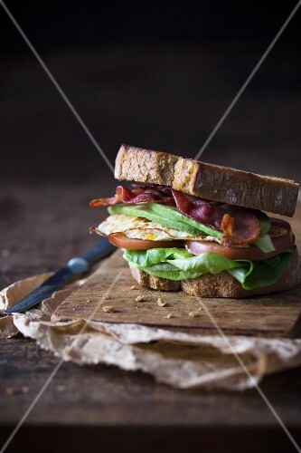 Sandwich with fried egg, bacon, avokado and tomato