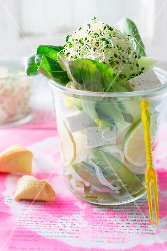 Salad with rice noodles, tofu, peapods, bok choy and shoots in a glass, with a fortune cookie next to it (Asia)