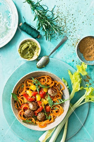 A meatball bowl with spiralized carrot spaghetti, tomatoes and rocket