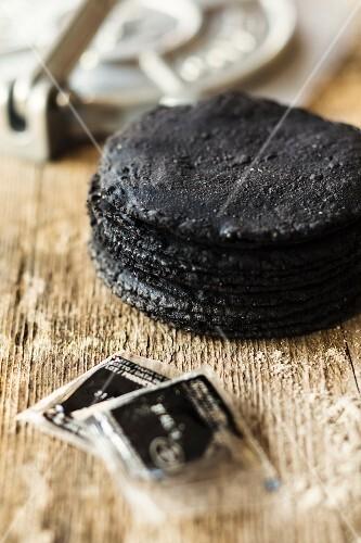 Black tortillas on a wooden surface (Mexico)