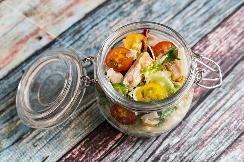 A pasta salad in a glass jar with tomatoes, chicken strips and pecorino