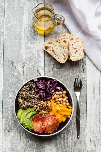A veggie bowl with quinoa, chickpeas, avocado, peppers, red cabbage and blood oranges