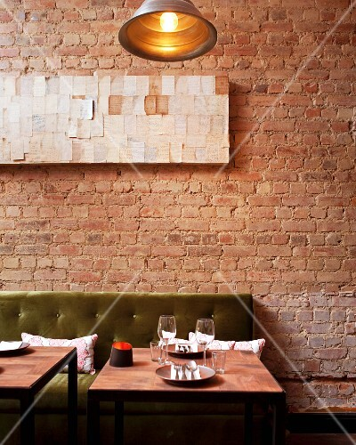 A table set for two in a restaurant with an exposed brick wall