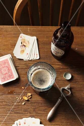 Bottle of Guinness poured into a large glass on a wooden table surrounded with bottle top, metal bottle opener, nuts and playing cards