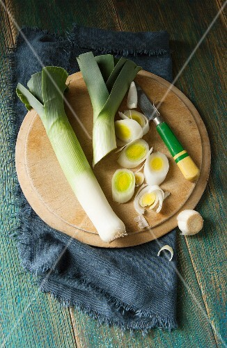 Overhead shot of two leeks on a round wooden chopping board being sliced by a retro wooden handled knife and navy cloth and green wooden background