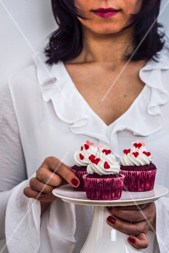 A woman with a white dress holding a cake stand full of red velvet cupcakes