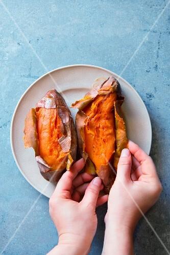 Hände entfernen Kartoffelschalen von ofengebackenen Süsskartoffeln
