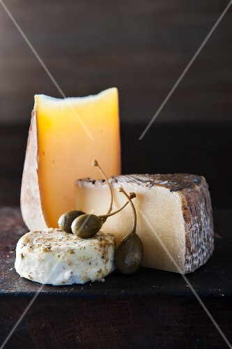 Artisanal cheese and fruit on wooden cutting board