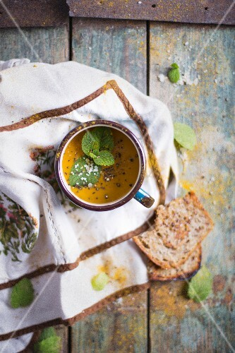 Carrot Creamy Soup in an enamel mug; decorated with fresh mint and sea salt flakes