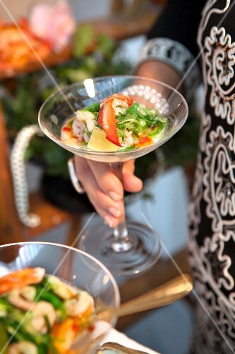 A woman holding a lobster salad with shrimp, lime and chilli in a cocktail glass