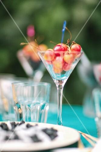 Glas mit Kirschen auf Gartentisch