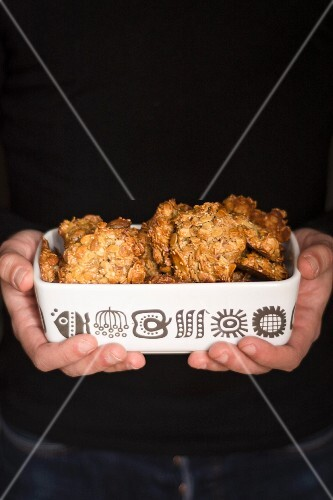 A man's hands holding a dish of oat biscuits