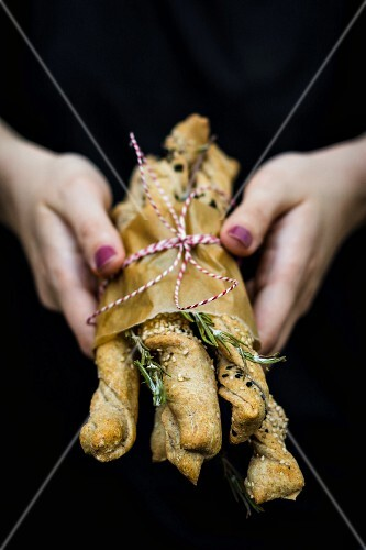 A woman's hands holding homemade bread sticks with rosemary and sesame seeds