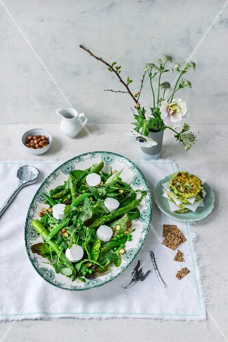 Spring salad with asparagus, goat's cheese, peas, rocket, lettuce, hazelnuts and zucchini patties