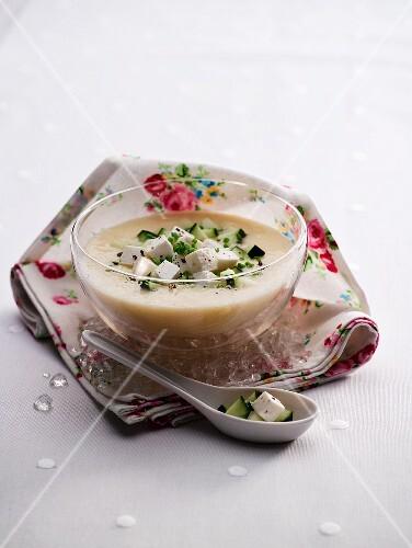 White gazpacho with feta cheese in a glass bowl