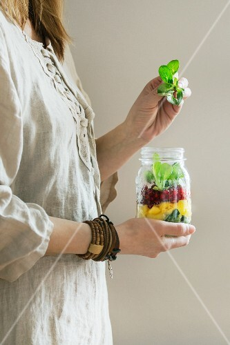 A woman in a linen dress holding a jar of fruit salad with mango, pomegranate seeds and lambs lettuce