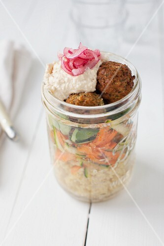 Vegan couscous salad with falafel, carrots, zucchini, houmous and red onions