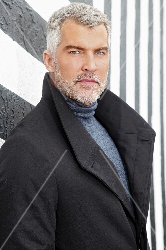 A man with grey hair wearing a roll-neck jumper and a coat in front of a black-and-white wall