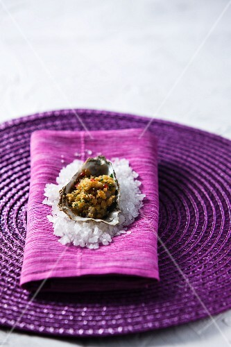 A breaded oyster on a bed of salt served on purple napkin and placemat
