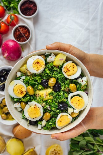 A woman holding a bowl of Mediterranean style potato salad with herbs and hard boiled eggs