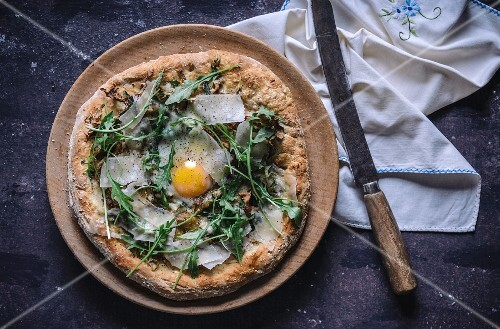 Pizza with fried egg, rocket and parmesan (top view)