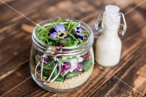 A quinoa salad with lambs lettuce, radicchio, rocket, croutons, goat's cheese and horned violets in a glass jar, with dressing in a glass bottle