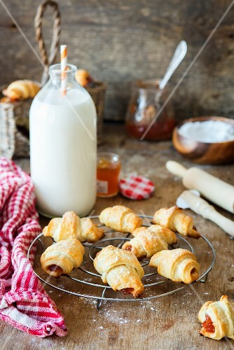 Croissants with jam on a cooling tray in front of a milk bottle
