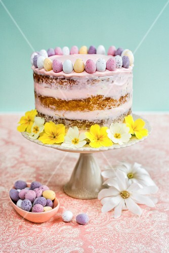 An Easter cake decorated with mini chocolate eggs and flowers