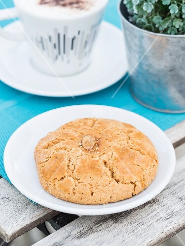 A Portuguese almond biscuit on a table with a cup of coffee