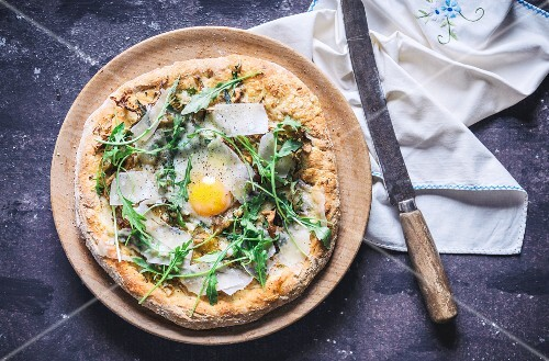 A pizza with rocket, fried egg and parmesan (seen from above)