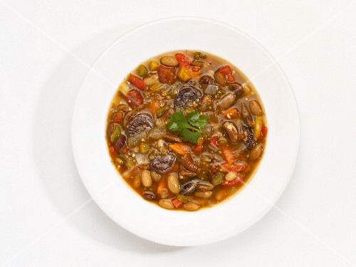 A bowl of bean soup in front of a white background (seen from above)