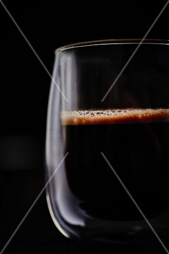 A cup of freshly brewed black coffee in front of a black background