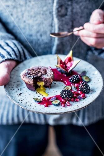 Chocolate cake with a liquid egg liqueur centre, raspberry sauce and autumn fruits
