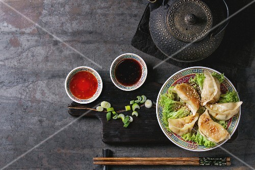 Gyozas potstickers on lettuce salad with sauces