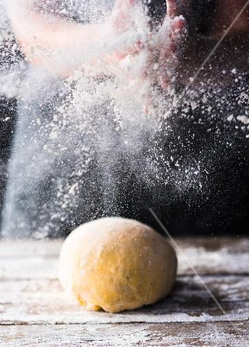 Teigkugel und Arbeitsfläche mit Mehl bestäuben