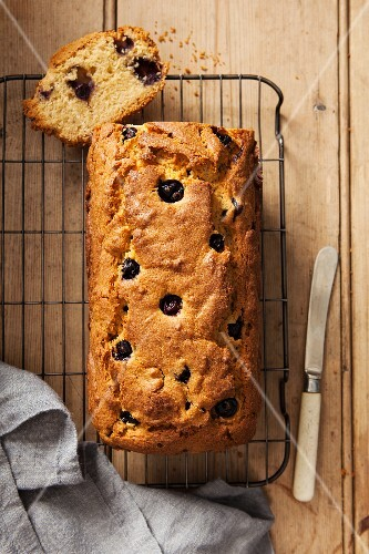 A sliced blueberry loaf cake on a wire cooling rack (seen from above)