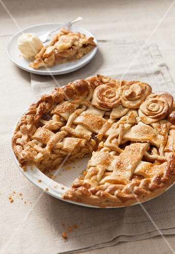 Apple pie with a dough lattice and pastry roses in a baking dish, cut