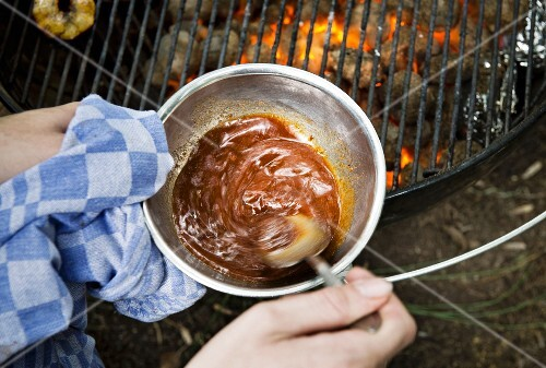 Babi Pangang sauce being heated on a grill
