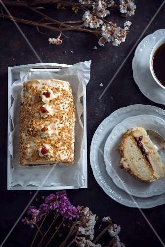 A sponge cake filled with vanilla cream, apple, mango and lingonberries, coated in hazelnut brittle (vegan)