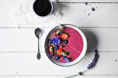 A smoothie bowl with fruits, edible flowers and gluten-free muesli (seen from above)
