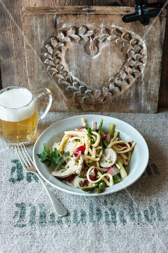 Veal sausage salad with spaetzle noodles, radishes and green asparagus
