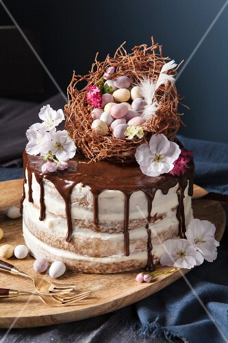 A naked sponge cake decorated with an Easter nest, chocolate eggs and blossoms