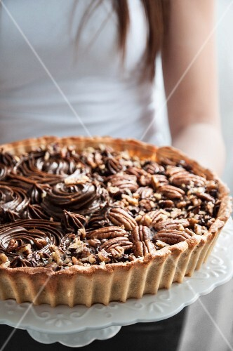A woman holding a chocolate and pecan tart on a cake stand