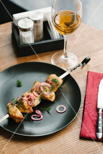 A chicken skewer with red onions and dill on a black plate